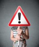 Молодая женщина держа дорожный знак возгласа Стоковые Изображения