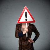 Молодая женщина держа дорожный знак возгласа Стоковое фото RF