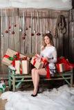 Молодая женщина держа подарок на стиле цвета рождества Стоковые Фото