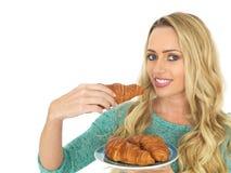Молодая женщина держа плиту свеже испеченных круассанов Стоковая Фотография
