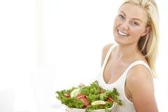 Молодая женщина держа салат Стоковая Фотография RF