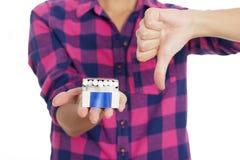 Молодая женщина держа сигареты и показывая большой палец руки вниз Стоковое Изображение RF