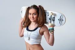 Молодая женщина держа скейтборд Стоковые Изображения RF