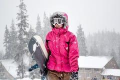 Молодая женщина держа сноуборд стоковые изображения