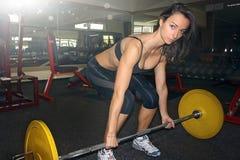 Молодая женщина держа штангу в положении deadlift на спортзале Стоковая Фотография RF