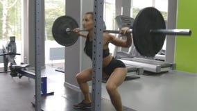 Молодая женщина держа штангу с тяжелыми весами на ее плечах по мере того как она сидит на корточках Сильная тренировка девушки в  акции видеоматериалы