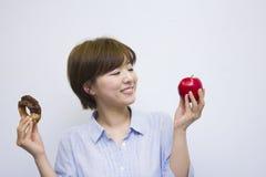 Молодая женщина держа яблоко и донут стоковые изображения