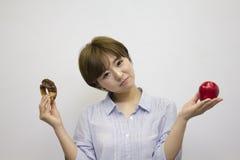 Молодая женщина держа яблоко и донут стоковые фото