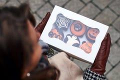 Молодая женщина держа colsed коробку различного хеллоуина ввела пирожные в моду стоковая фотография