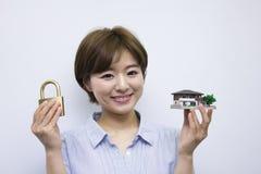 Молодая женщина держа padlock и дом моделируют стоковая фотография rf