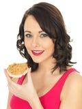 Молодая женщина есть арахисовое масло на шутихе Стоковое Фото