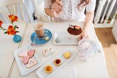 Молодая женщина есть десерт и выпивая latte на таблице Стоковое Изображение RF