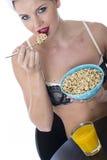 Молодая женщина есть женское бельё хлопий для завтрака Стоковое Фото