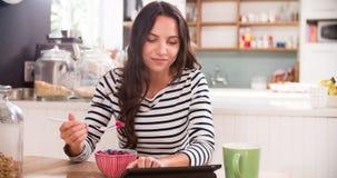 Молодая женщина есть завтрак пока использующ таблетку цифров Стоковые Фото
