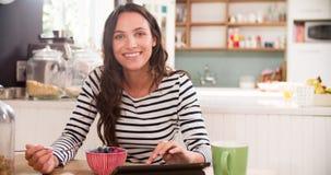 Молодая женщина есть завтрак пока использующ таблетку цифров Стоковые Изображения