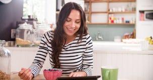 Молодая женщина есть завтрак пока использующ таблетку цифров Стоковое Фото