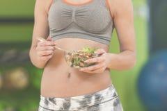 Молодая женщина есть здоровый салат овощей после разминки Фитнес и здоровая концепция образа жизни стоковое фото