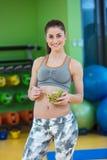 Молодая женщина есть здоровый салат овощей после разминки Фитнес и здоровая концепция образа жизни стоковая фотография
