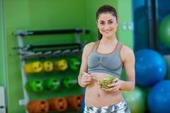 Молодая женщина есть здоровый салат овощей после разминки Фитнес и здоровая концепция образа жизни стоковое фото rf
