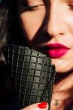 Молодая женщина есть мороженое конуса темной черноты Женщина портрета конца-вверх с красными губами Стоковая Фотография