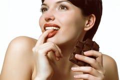 Молодая женщина есть очень вкусный шоколад Стоковое Изображение