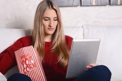 Молодая женщина есть попкорн и смотря кино на таблетке Стоковые Фото