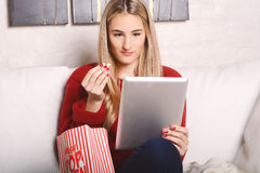 Молодая женщина есть попкорн и смотря кино на таблетке Стоковые Изображения
