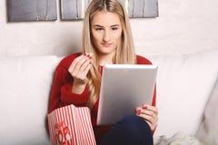 Молодая женщина есть попкорн и смотря кино на таблетке Стоковые Изображения RF