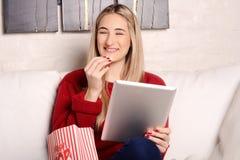 Молодая женщина есть попкорн и смотря кино на таблетке Стоковая Фотография RF