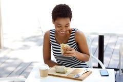 Молодая женщина есть сандвич на внешнем кафе Стоковая Фотография RF