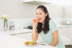 Молодая женщина есть салат в кухне Стоковое Изображение RF