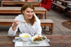 Молодая женщина есть суп и салат в внешнем ресторане. стоковая фотография rf