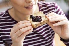 Молодая женщина есть хлеб здравицы с вареньем Стоковые Фото