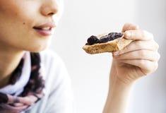 Молодая женщина есть хлеб здравицы с вареньем Стоковое фото RF