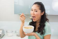 Молодая женщина есть хлопья в кухне Стоковая Фотография RF