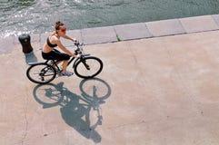 Молодая женщина ехать велосипед на каменном обваловке реки Стоковая Фотография