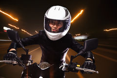 Молодая женщина ехать мотоцикл через улицы Пекина, свет отстает стоковое фото rf