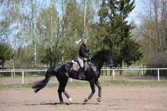 Молодая женщина ехать черная лошадь Стоковые Изображения