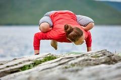 Молодая женщина делая баланс руки представления йоги на каменном близко большом реке Стоковые Изображения