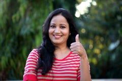 Молодая женщина делая большие пальцы руки вверх показывать на outdoors Стоковая Фотография RF