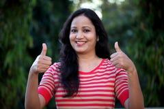 Молодая женщина делая большие пальцы руки вверх показывать на outdoors Стоковое Изображение RF
