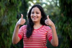 Молодая женщина делая большие пальцы руки вверх показывать на outdoors Стоковые Изображения RF
