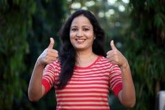 Молодая женщина делая большие пальцы руки вверх показывать Стоковые Фотографии RF