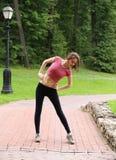Молодая женщина делая гимнастику outdoors Стоковая Фотография