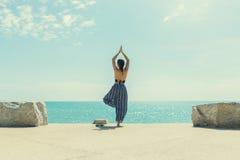 Молодая женщина делая йогу в пляже Стоковое Изображение RF