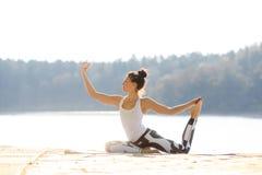 Молодая женщина делая йогу около озера outdoors, раздумье Фитнес спорта и работать в природе заход солнца Румынии пущи осени Стоковое фото RF