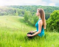 Молодая женщина делая йогу работает внешнее Йога красивой девушки практикуя в парке Стоковые Фотографии RF