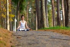 Молодая женщина делая йогу работает в парке города осени Концепция образа жизни здоровья Стоковое Фото