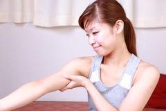 Молодая женщина делая массаж руки собственной личности стоковое изображение