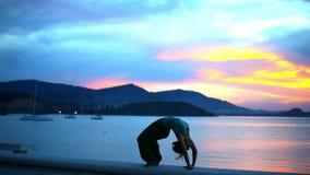 Молодая женщина делая мост йоги, силуэт захода солнца акции видеоматериалы